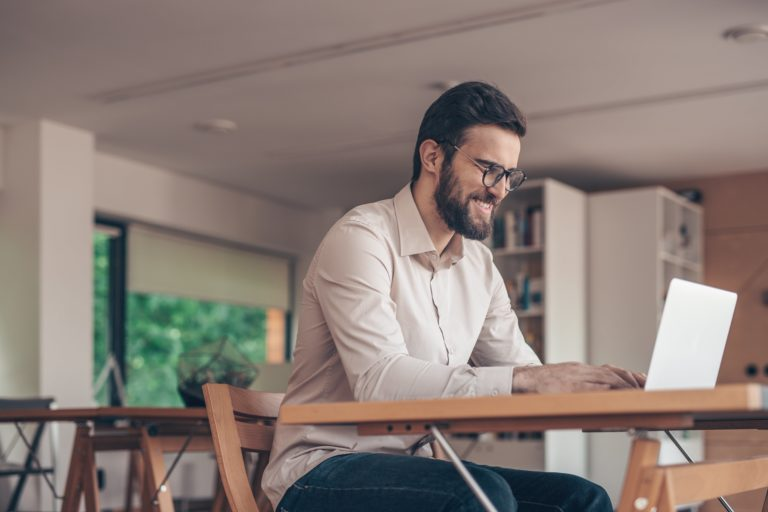 smiling-businessman-with-laptop-2BNSVH8-min